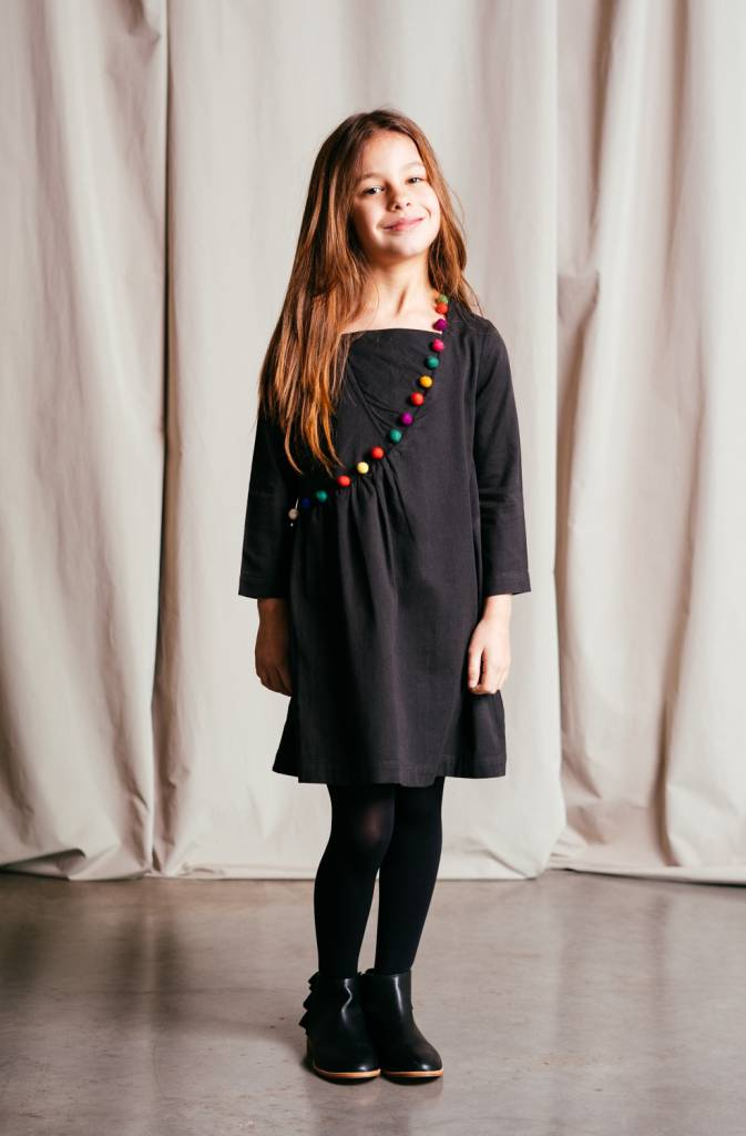 Organic cotton sateen dress with a colourful pom-pom trim accent.