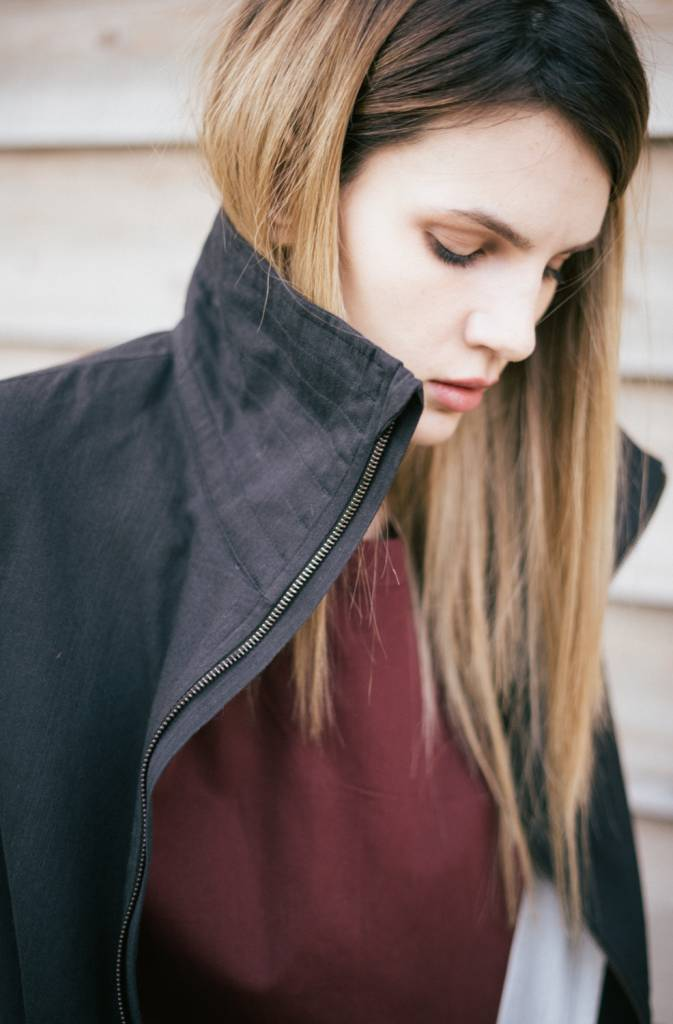 Zip up coat with high funnel neck, side pockets and back slit.