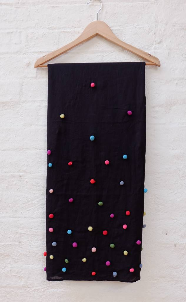 Organic Cotton shawl featuring scattered pom-pom accents.