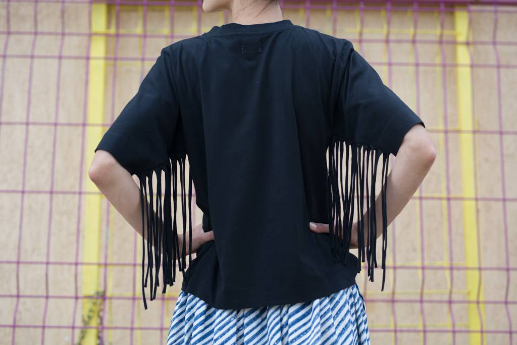 Organic cotton jersey tee with high round neck opening and long fringing detail at under-sleeve seam.